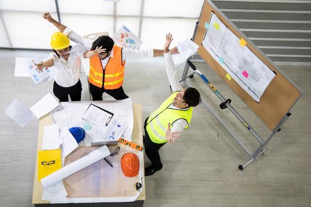 Succesgroep ingenieurs met het document gooien na het sluiten van het project.