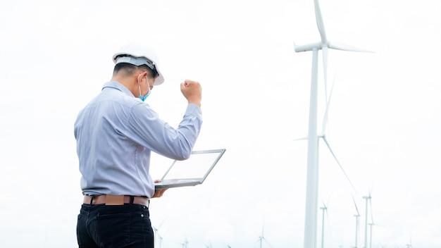 Succesingenieur windmolens die gezichtsmasker dragen en aan laptop werken met de windturbine op achtergrond
