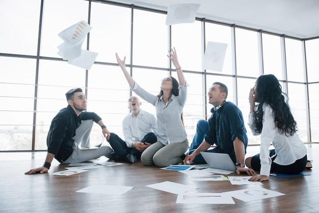 Successtrategie samen. vrolijke bedrijfscollega's die documenten werpen op creatief kantoor.