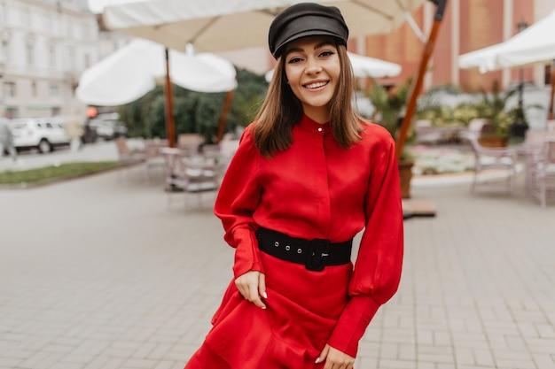 Succesvol aantrekkelijk meisje dat met goede stijl onderaan straat loopt. portret van europees model in modieuze dieprode satijnen jurk