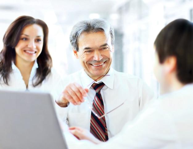 Succesvol businessteam van drie die op kantoor zitten en werk plannen