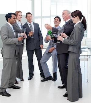 Succesvol commercieel team dat de cork op een fles champagne knalt