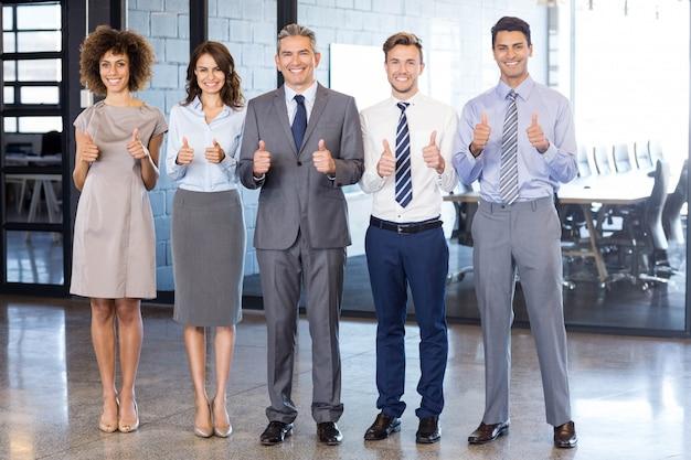 Succesvol commercieel team dat hun duimen tegenhoudt terwijl het vieren van overwinning in bureau