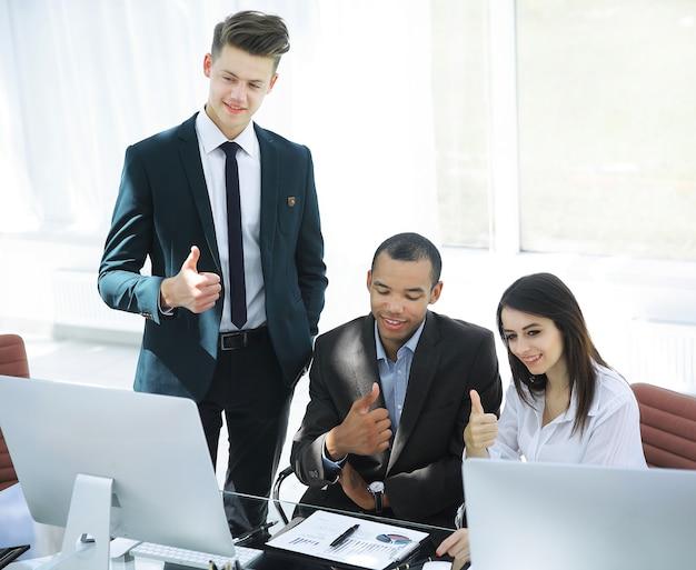 Succesvol commercieel team dat laptop het scherm bekijkt en duim toont.
