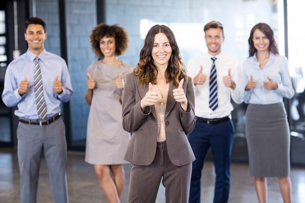 Succesvol commercieel team die hun duimen tegenhouden terwijl het vieren van overwinning in bureau