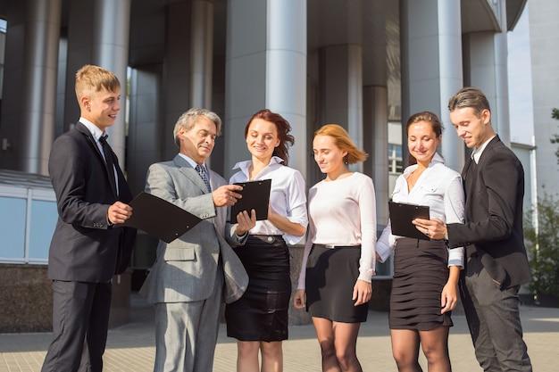 Succesvol commercieel team met tabletten op een achtergrond van bureau