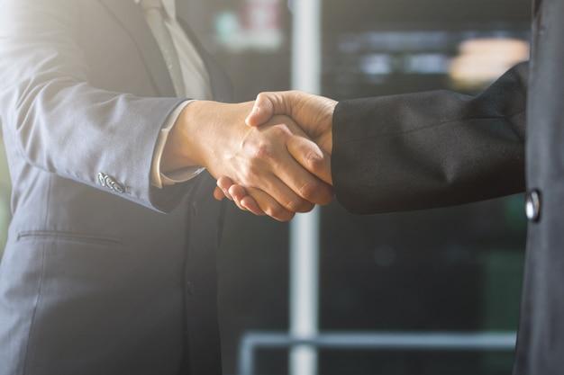 Succesvol onderhandel en handdrukconcept, twee zakenman schudt hand met partner aan vieringsvennootschap en groepswerk, zakelijke deal