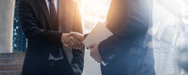 Succesvol onderhandelen en prestatieconcept, twee zakenmensen schudden de hand na een gesprek en succes in investeringsdeal