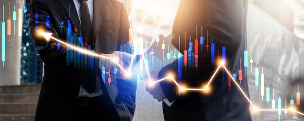 Succesvol onderhandelen en prestatieconcept, twee zakenmensen schudden de hand na een gesprek en succes in investeringsovereenkomst met financiële grafiek
