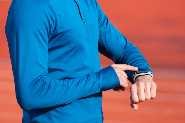 Succesvol runner kijken naar hartslagmeter smart watch, close-up.