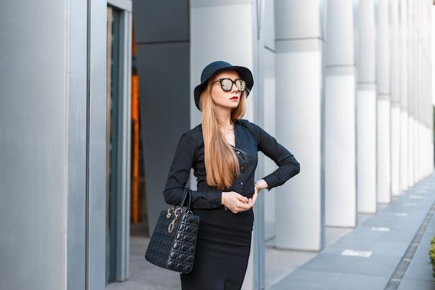 Succesvol stijlvol jong meisje in een strikte manierkleren met een hoed