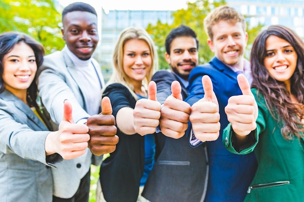 Succesvol team van bedrijfsmensen die duimen tonen