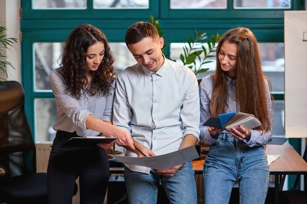 Succesvol team van jonge kaukasische ingenieur die zich dichtbij houten lijst bevindt en over nieuw project spreekt. bedrijfsconcept.