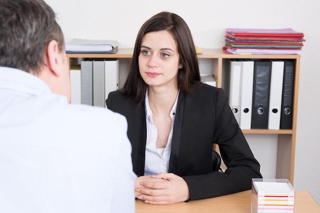 Succesvol teamwerk: bedrijfsman en vrouwenzitting bij bureau die over rapporten en financiën spreken.