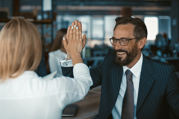 Succesvol teamwerk vieren vrolijke zakenman in bril geven high five met collega vrouw permanent terug op de voorgrond. teamwerk concept.