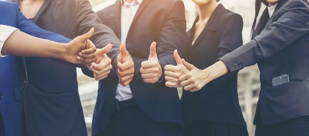Succesvol van zakenteamwerk dat duimschrift toont. bedrijfsconcept.