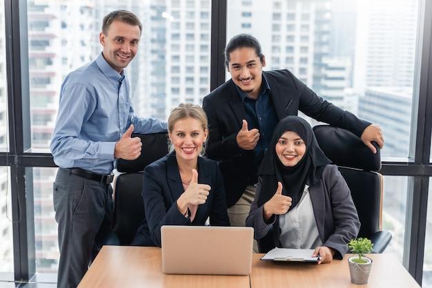 Succesvol zakenmensen met multi-etnisch werk op de werkplek duimen omhoog met felicitaties voor hun succes met een gevoel van plezier en glimlachen