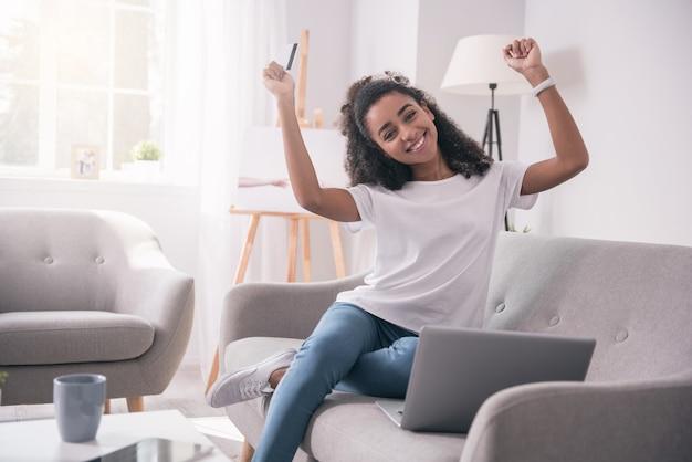 Succesvolle aankoop. aangename jonge studente die haar emoties toont terwijl ze blij is met haar aankoop op internet