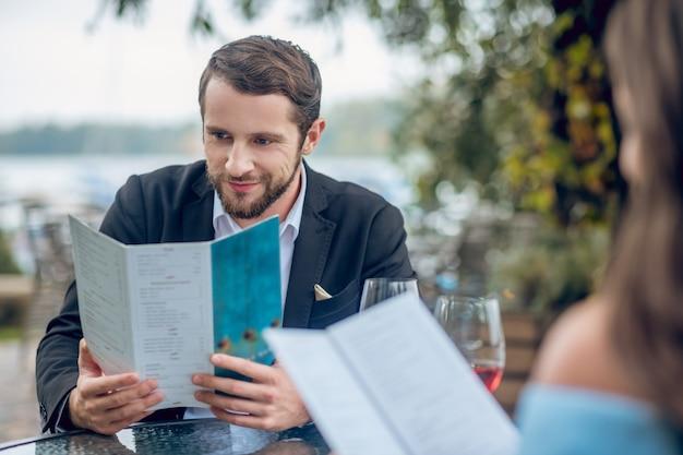 Succesvolle aantrekkelijk geïnteresseerde man menu en vrouw in zomerterras buiten kijken