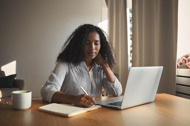 Succesvolle aantrekkelijke jonge afro-amerikaanse zakenvrouw in stijlvol shirt zit op haar werkplek voor open draagbare computer en het maken van aantekeningen in haar dagboek, met doordachte gezichtsuitdrukking