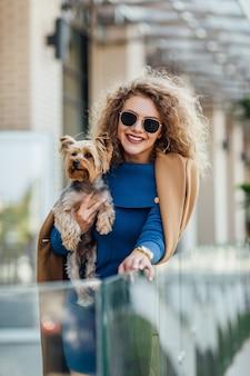 Succesvolle aantrekkelijke vrouw die een naaktjas draagt met yorkshire terriër