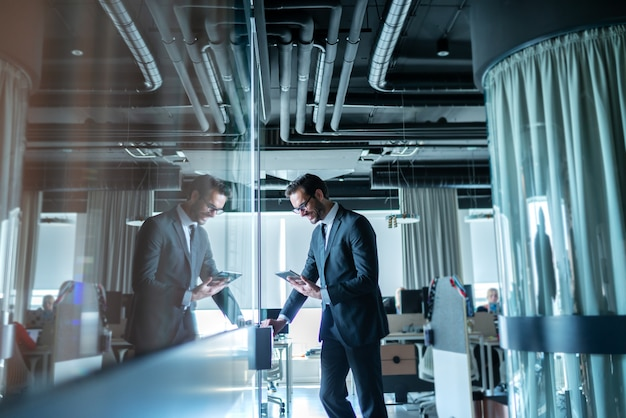 Succesvolle advocaat gekleed in formele kleding staat voor zijn kantoor en gebruikt tablet voor werk.