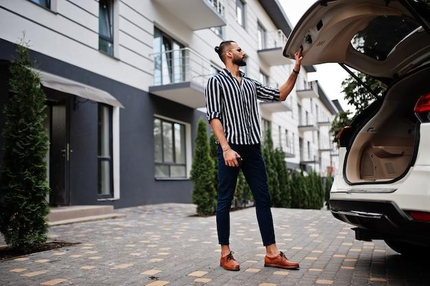 Succesvolle arabische man dragen in gestreept overhemd en zonnebril gesloten kofferbak van zijn witte suv-auto. stijlvolle arabische mannen in transport.