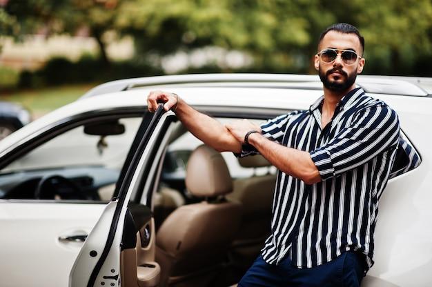 Succesvolle arabische mannenkleding in gestreept overhemd en zonnebril poseren in de buurt van zijn witte suv-auto. stijlvolle arabische mannen in transport.