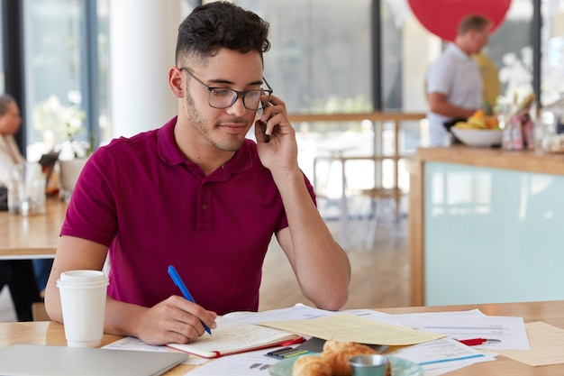 Succesvolle architect denkt na over projectimplementatie, bespreekt ideeën met collega via mobiele telefoon, maakt records in notitieblok, geniet van frisdrank in gezellige bistro. mannelijke ontwerper werkt in café