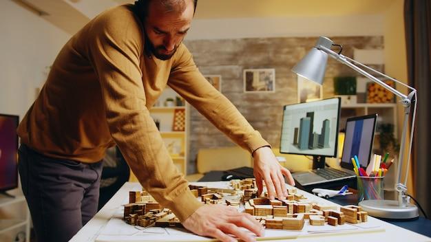 Succesvolle architect die aan de telefoon praat terwijl hij een stadsmodel bouwt in zijn thuiskantoor.