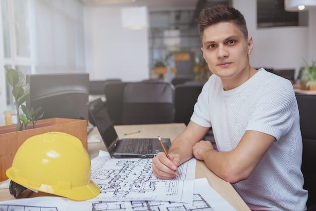 Succesvolle architect die op blauwdrukken op kantoor werkt