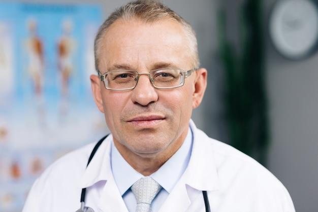 Succesvolle arts in witte laboratoriumjas die naar voren kijkt en glimlacht in het ziekenhuiskantoor