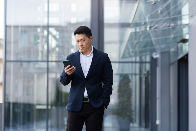 Succesvolle aziatische baas correspondeerde serieus aan de telefoon in een pak