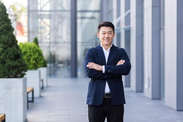 Succesvolle aziatische baas in de buurt van het kantoor kijkt naar de camera met gekruiste armen glimlacht en verheugt zich over succes