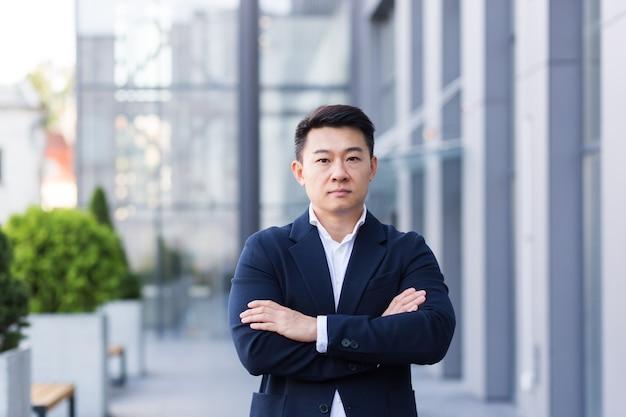 Succesvolle aziatische baas in de buurt van kantoor kijken naar camera met gekruiste armen van serieuze zakenman