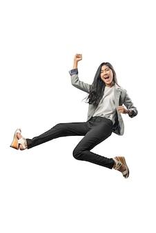 Succesvolle aziatische bedrijfsvrouw die en opgeheven wapen springt aan de lucht