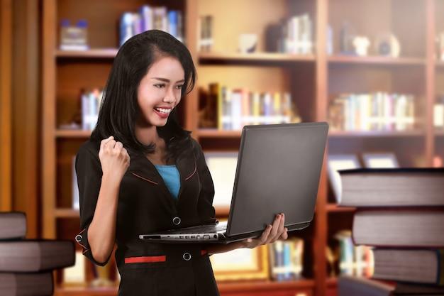 Succesvolle aziatische bedrijfsvrouw die zich met laptop bevindt