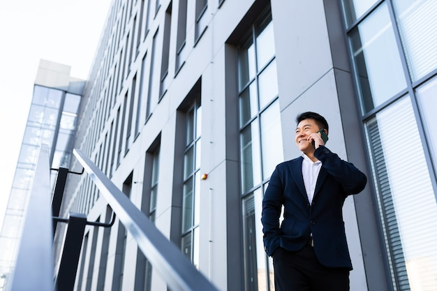 Succesvolle aziatische zakenman die aan de telefoon praat in de buurt van het kantoorcentrum, glimlachend en blij wegkijkend