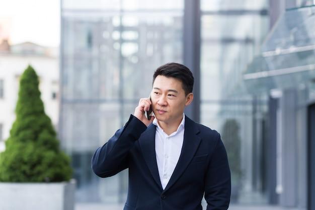 Succesvolle aziatische zakenman die op een mobiele telefoon praat terwijl hij in de buurt van het kantoor van een grote moderne, serieuze en peinzende werknemer loopt