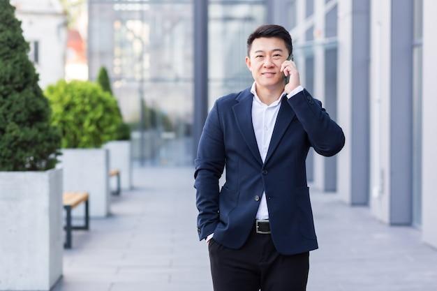 Succesvolle aziatische zakenman die op mobiele telefoon praat terwijl hij in de buurt van een groot modern kantoor loopt, een vrolijke glimlachende werknemer en naar de camera kijkt