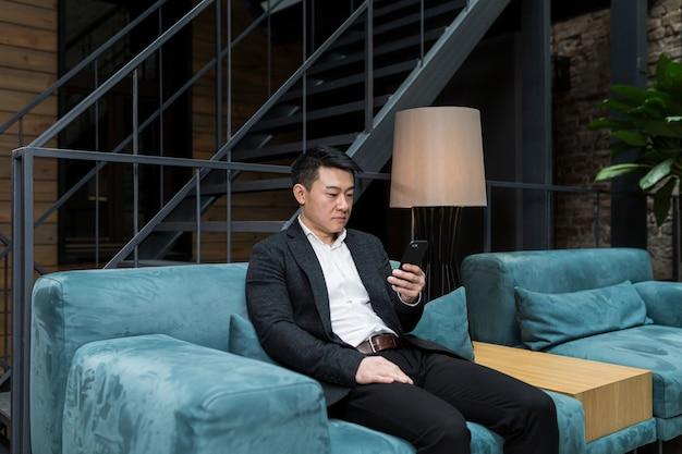 Succesvolle aziatische zakenman in een zwart pak werkt op een laptop ontspant in een restaurant
