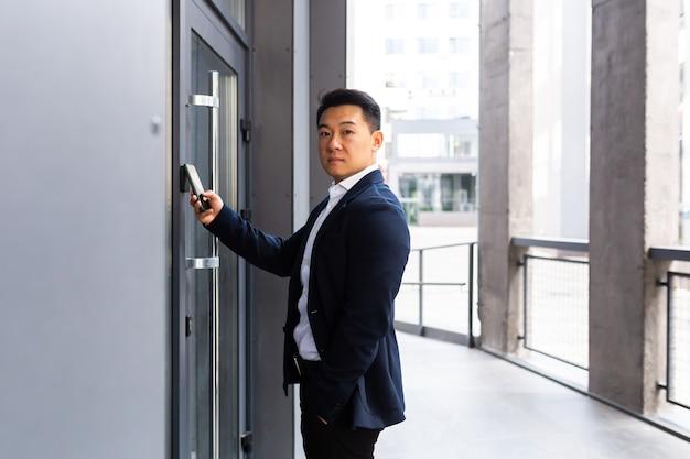 Succesvolle aziatische zakenman opent de deur van het kantoorcentrum met behulp van een smartphone en nfc-applicatie