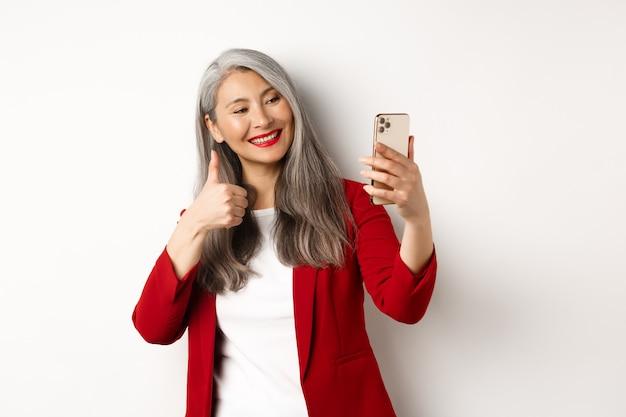 Succesvolle aziatische zakenvrouw in rode blazer, selfie te nemen op smartphone met duim-omhoog, goedkeuring tonen, staande op witte achtergrond.