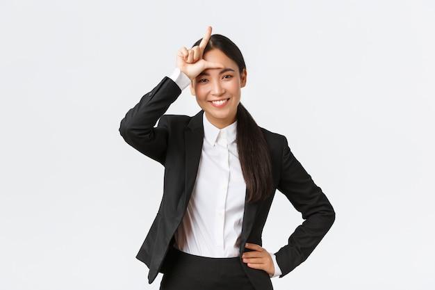 Succesvolle aziatische zakenvrouw in zwart pak bespotten haar rivalen, verliezer teken tonen als winnen en vieren overwinning op concurrenten, staande tevreden over witte achtergrond