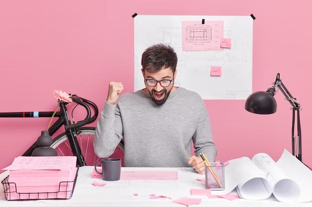 Succesvolle bebaarde man verheugt zich op het afronden van projectwerk balt vuisten staart naar papieren poses in coworking-ruimte omringd met memostickers