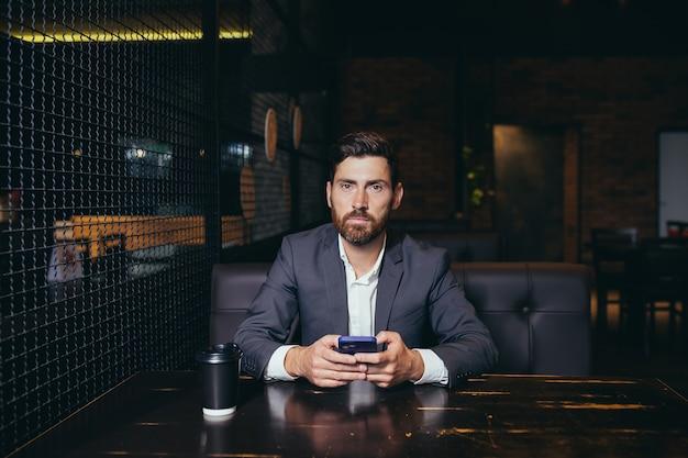Succesvolle bebaarde zakenman correspondeerde in messenger op mobiele applicatie in restaurant