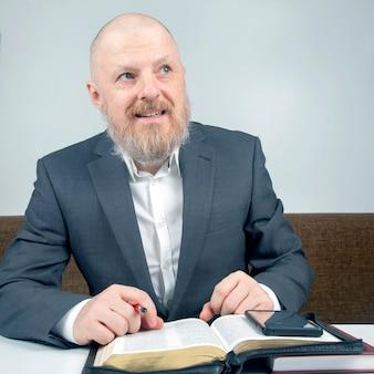 Succesvolle bebaarde zakenman met een boek en zijn smartphone