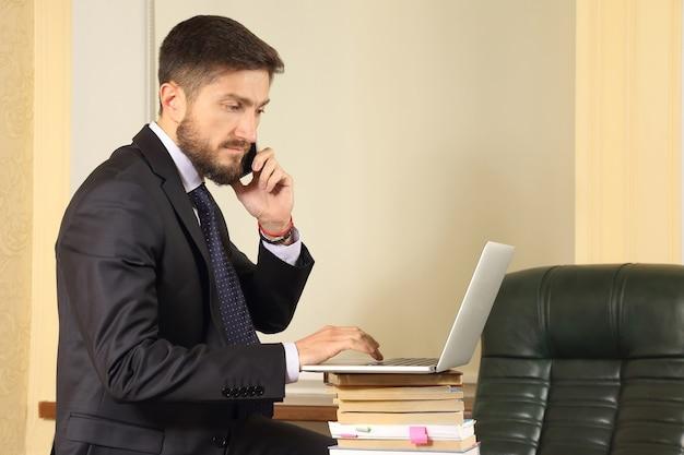Succesvolle bedrijfsmens die in bureau met laptop werkt