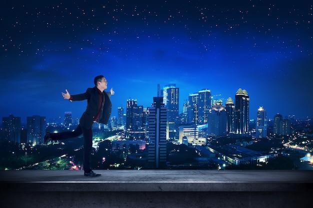 Succesvolle bedrijfsmens op het dak bij nacht