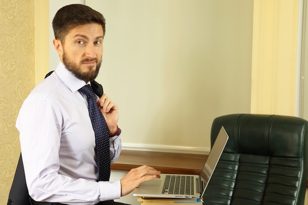 Succesvolle bedrijfsmens op kantoor met laptop